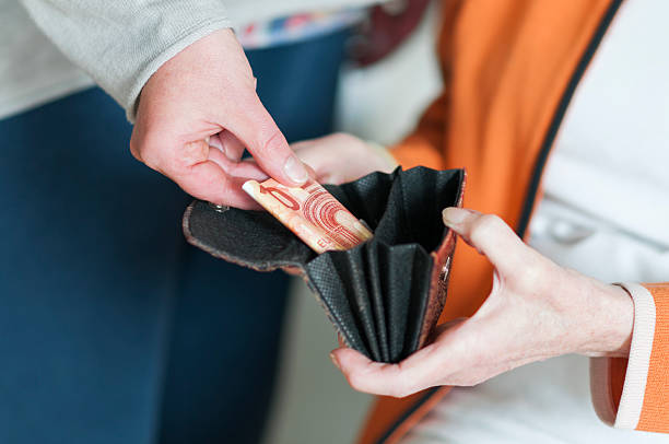 Woman takes money from the purse of a Senior women stock photo