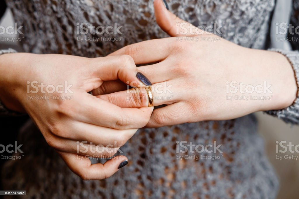 woman takes off an engagement ring, family conflict,  close-up woman takes off an engagement ring, family conflict,  close-up Adult Stock Photo