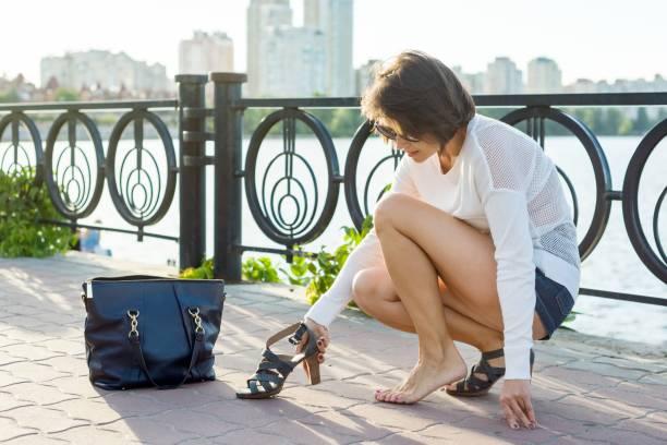 frau zieht ihre schuhe. hintergrund-fluss, urbanen stil. - damenschuhe 44 stock-fotos und bilder