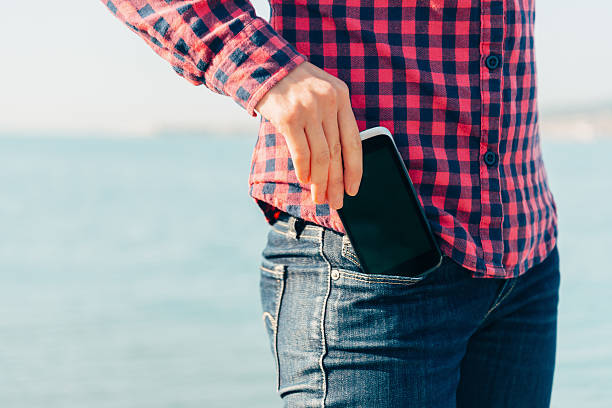 woman takes out phone of her pocket on beach - pocket stock photos and pictures