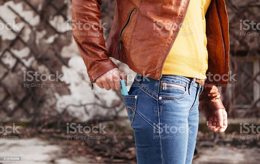 Woman takes out smartphone of her rear pocket of jeans stock photo