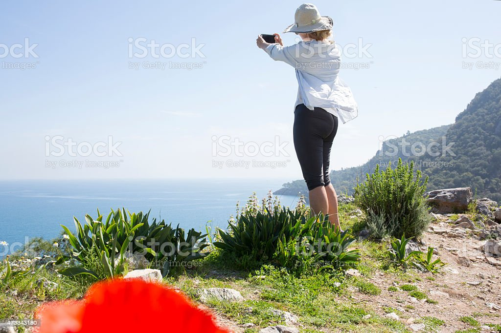 Woman takes pic of sea from mountain ridge crest stock photo