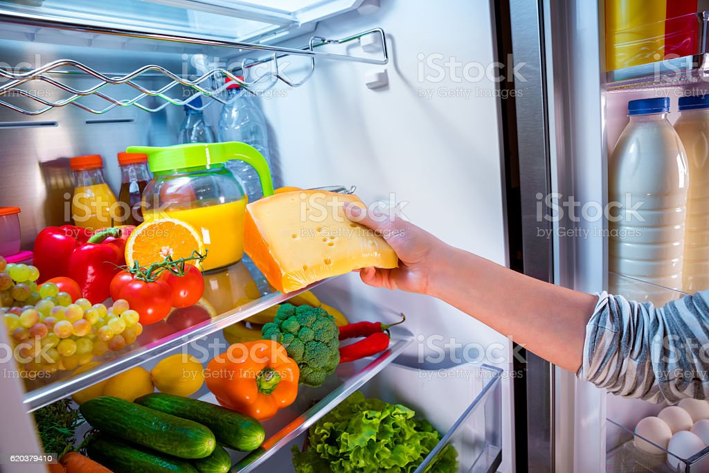 Woman takes the piece of cheese from the open refrigerator foto de stock royalty-free