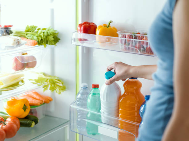 Woman taking a bottle of fresh milk from the fridge, nutrition and diet concept stock photo
