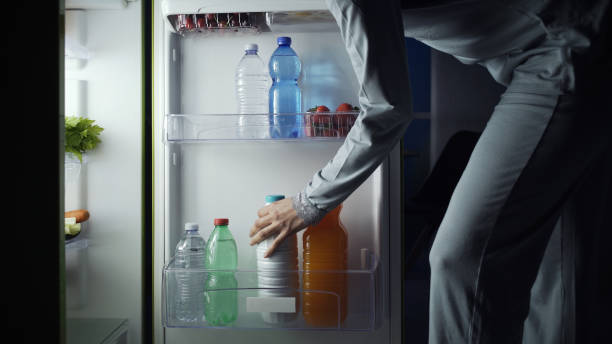 Woman taking a bottle of milk from the fridge late at night, lifestyle and diet concept stock photo