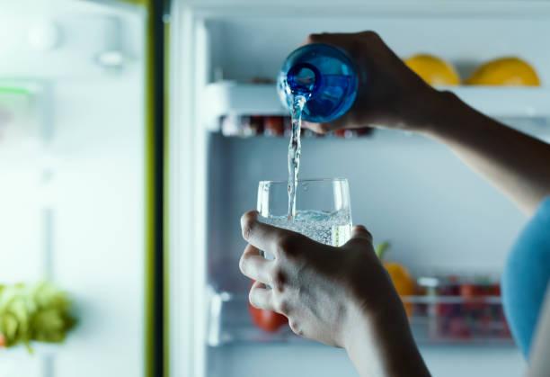 Mulher tomando uma garrafa de água da geladeira e coloca-lo em um vidro - foto de acervo