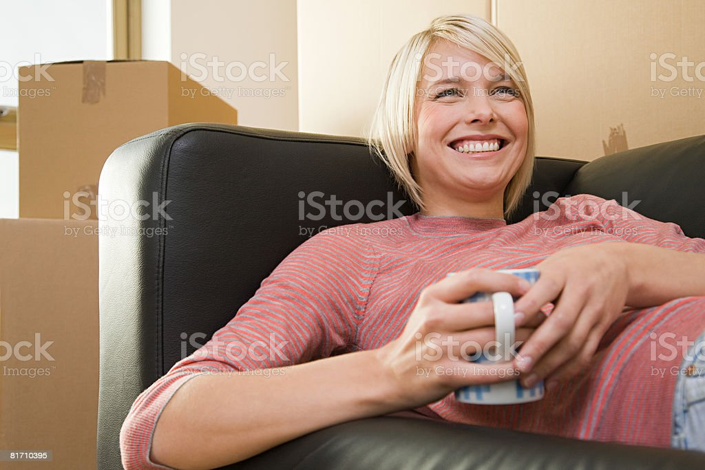 Woman taking a break from moving in royalty-free stock photo