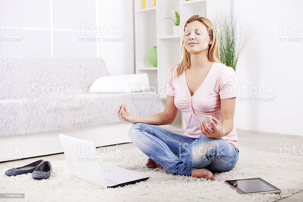 Woman taking a break from working and meditating royalty-free stock photo