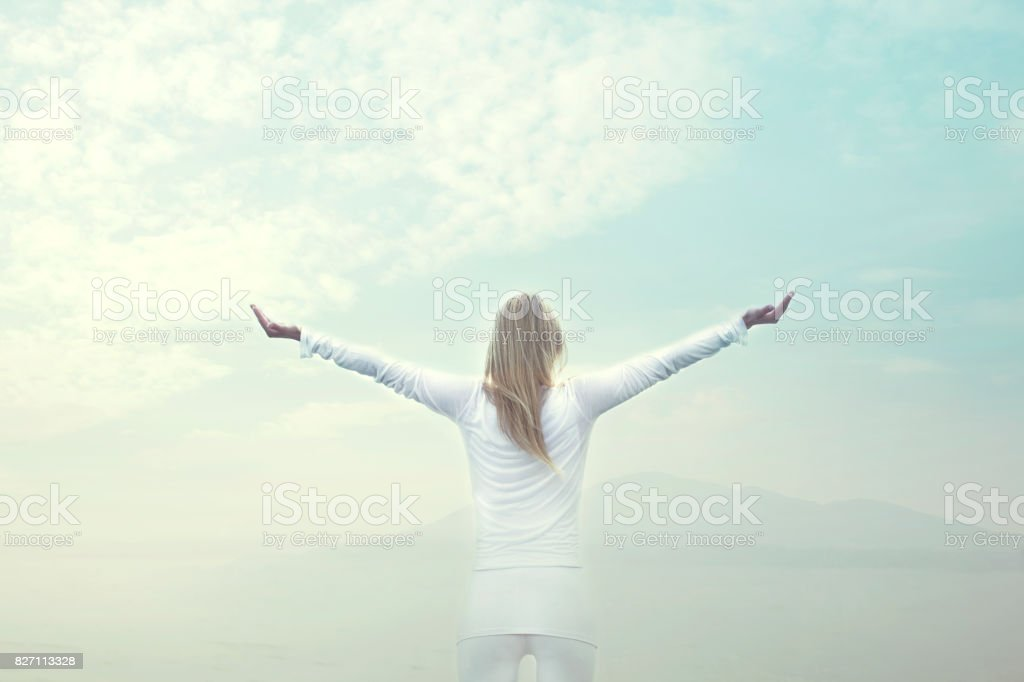 woman taking a breath in front of a blue sky stock photo
