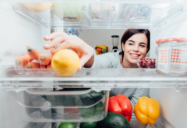 woman taking a lemon out of the fridge - fridge fotografías e imágenes de stock