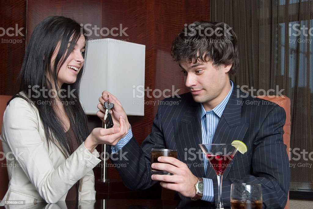 A woman taking a mans keys while he's drinking at a bar stock photo