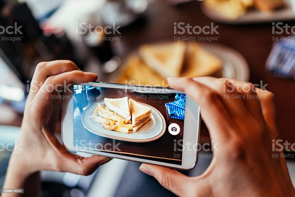 Woman taking a photo of her sandwich stock photo