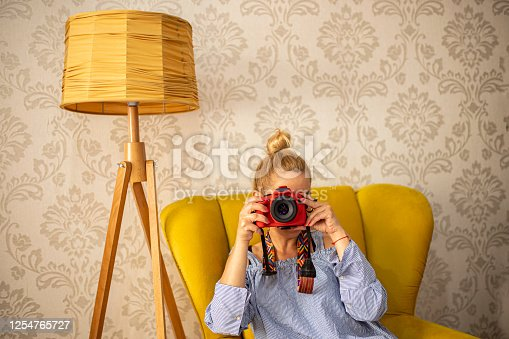 Woman sitting in the vintage living room and having a photo