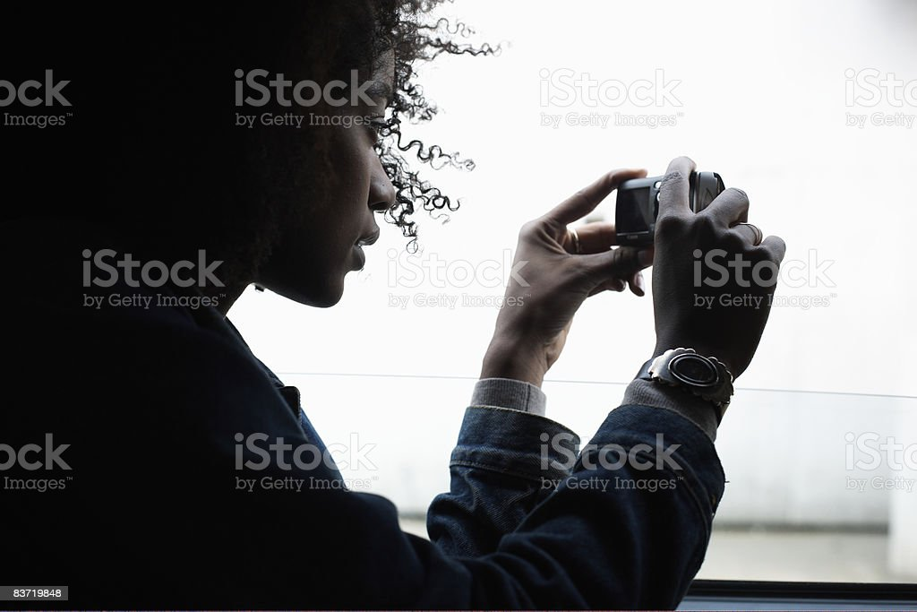 Woman taking a photograph from window royalty-free stock photo