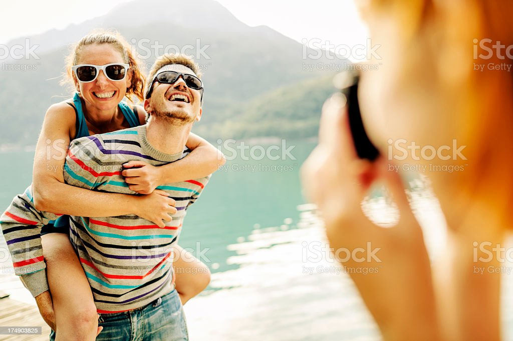 A woman taking a photograph of her two friends royalty-free stock photo
