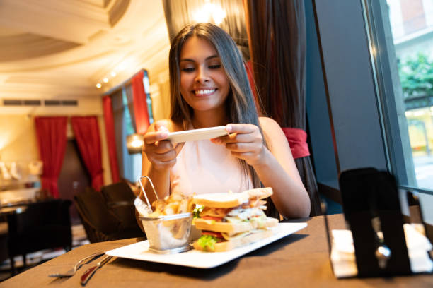 woman taking a picture of her food at a restaurant - foodie stock photos and pictures