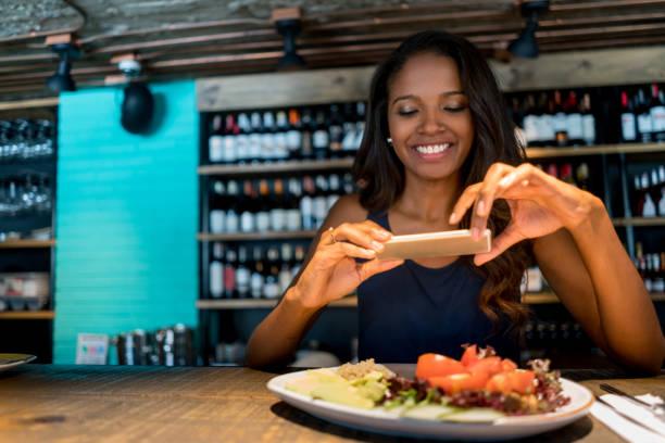 Femme de prendre une photo de sa nourriture dans un restaurant - Photo