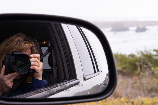 Woman holding a 35mm camera up to face taking a picture of self in rearview mirror while also seeing the ocean in the background