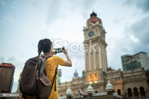 Young woman with backpack taking a picture of the Sultan Abdul Samad Building in Kuala Lumpur, Malaysia