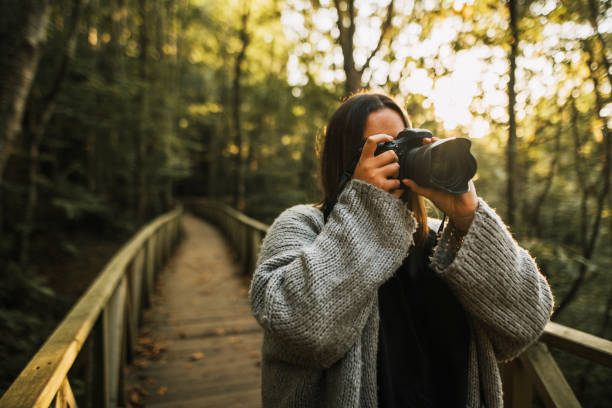Woman taking a picture with a DSLR camera stock photo