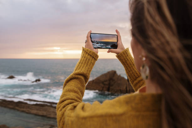 Woman taking a picture with a smartphone stock photo