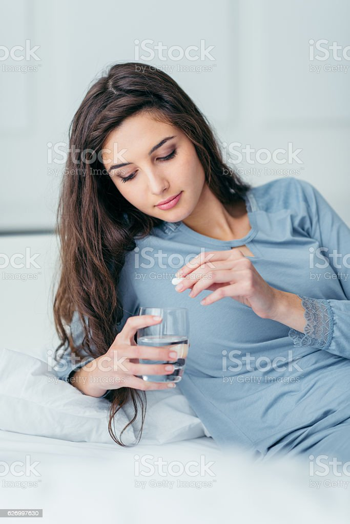 Woman taking a pill stock photo