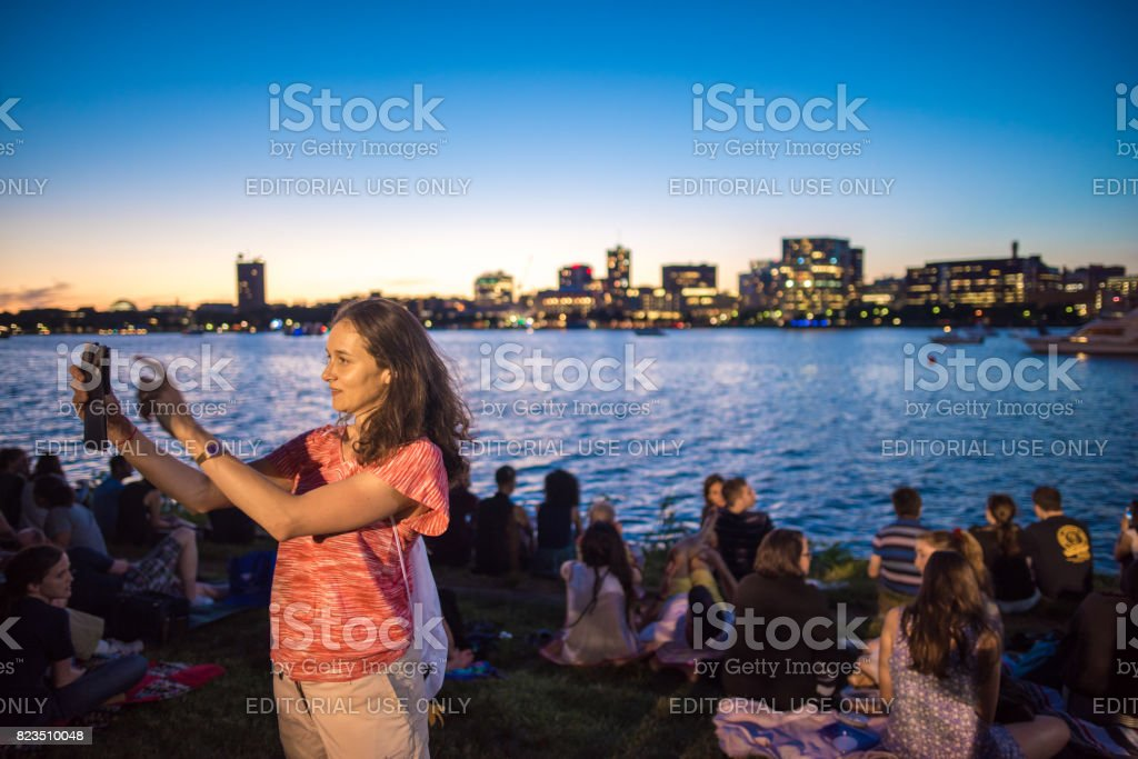 Woman taking a selfie in Esplanade Park in Boston during the Boston Pops concert stock photo