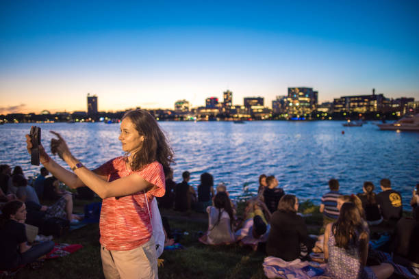 woman taking a selfie in esplanade park in boston during the boston pops concert - concert selfie stock photos and pictures