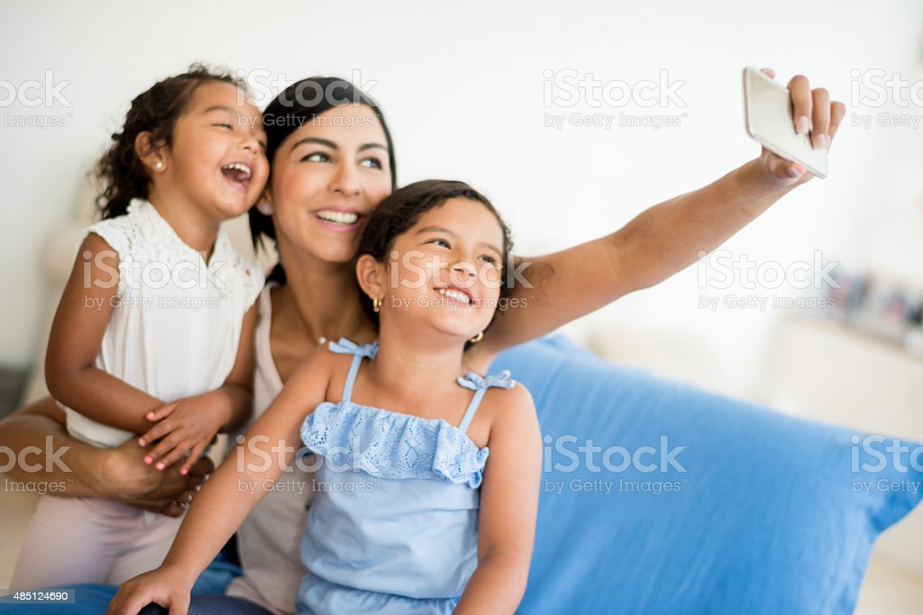Woman taking a selfie with her daughters stock photo
