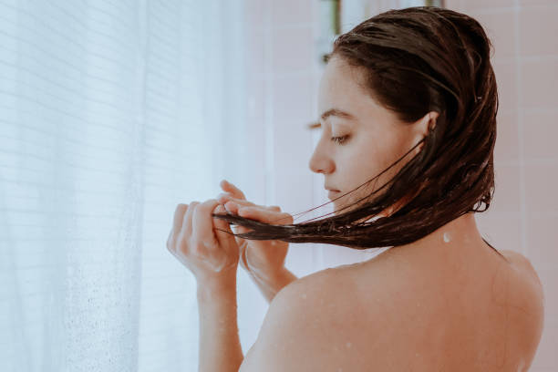 Woman taking a shower and washing her hair at home stock photo