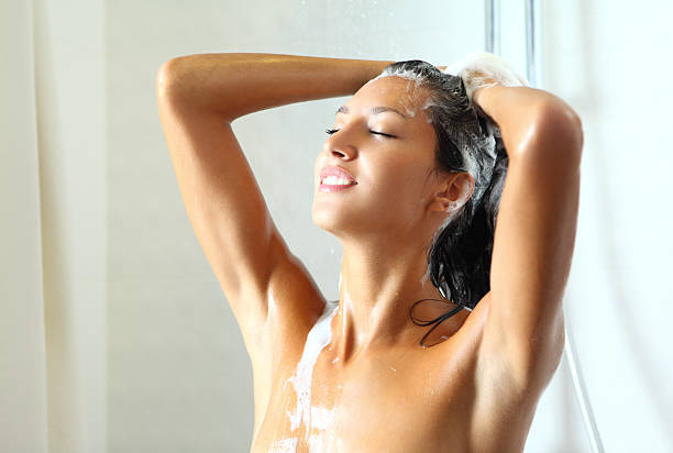 donna prendendo una doccia. - lavarsi i capelli foto e immagini stock