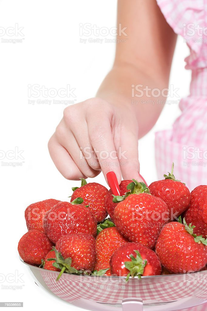 Woman taking a strawberry from bowl royalty-free stock photo