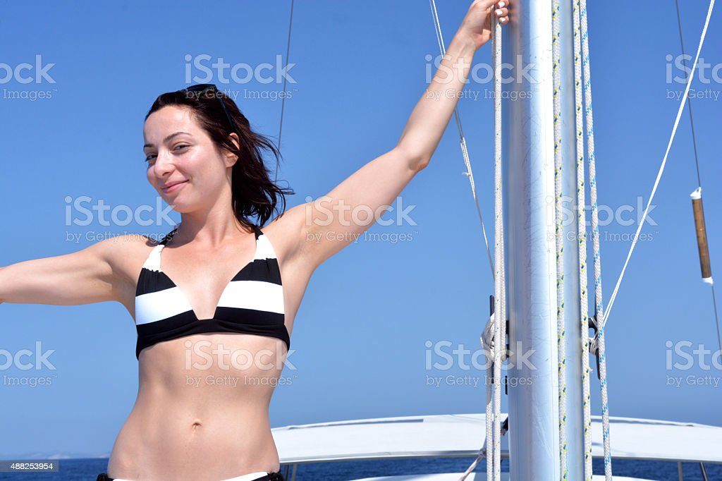 Woman taking a sunbath on deck of a yacht stock photo