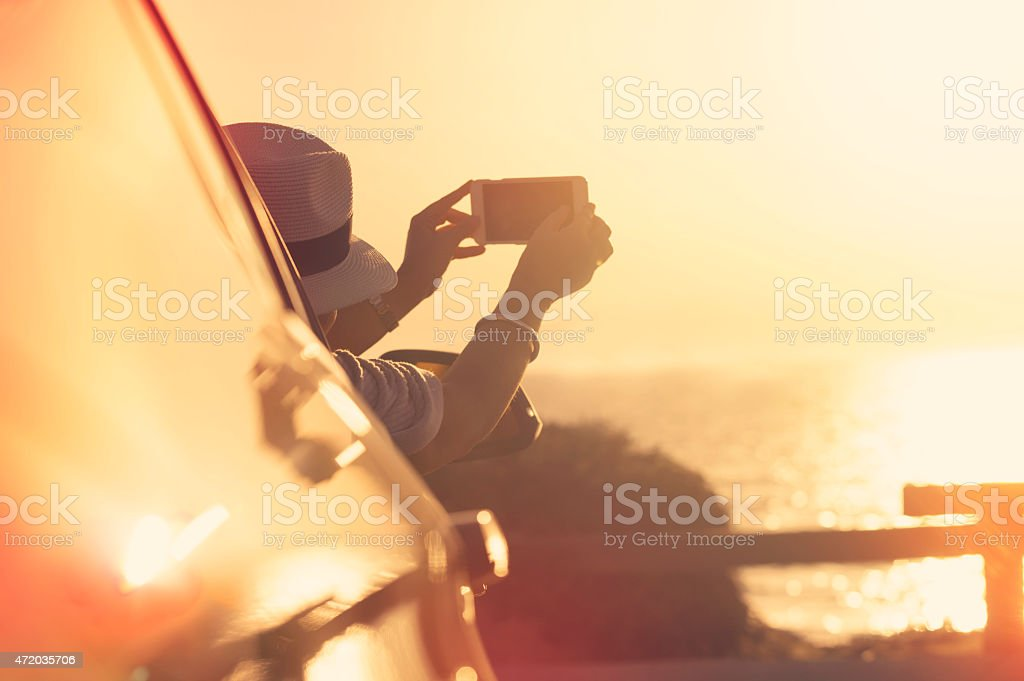 Woman taking a sunset photo in a car. stock photo