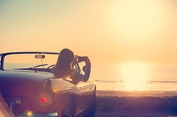 Woman taking a sunset photo in a convertible car. stock photo