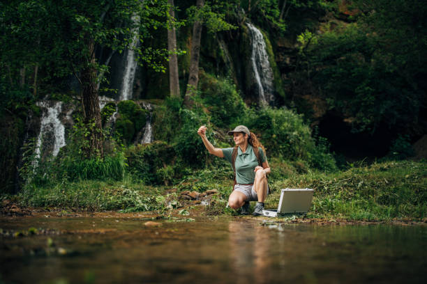 Woman Taking a Water Sample Woman Biological Researcher Taking a Water Sample wildlife reserve stock pictures, royalty-free photos & images