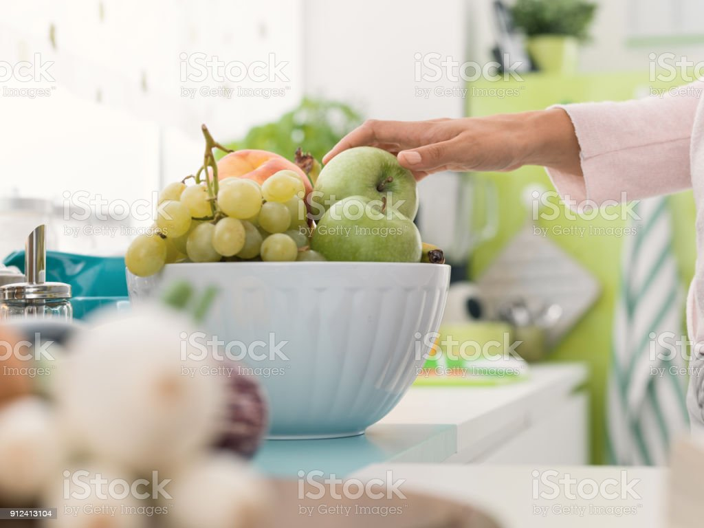 Woman taking an apple from a fruit bowl stock photo