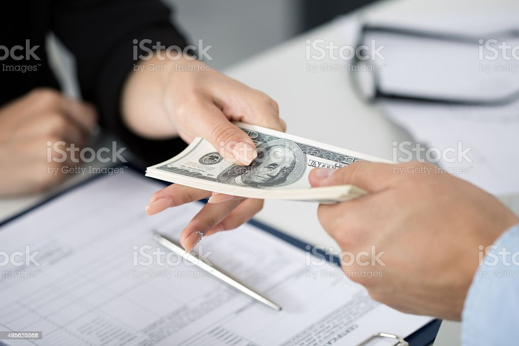 Woman taking batch of hundred dollar bills stock photo