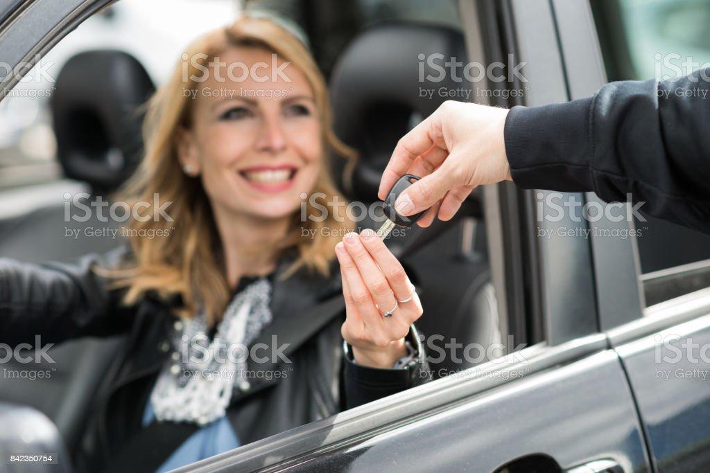 Woman taking car keys stock photo