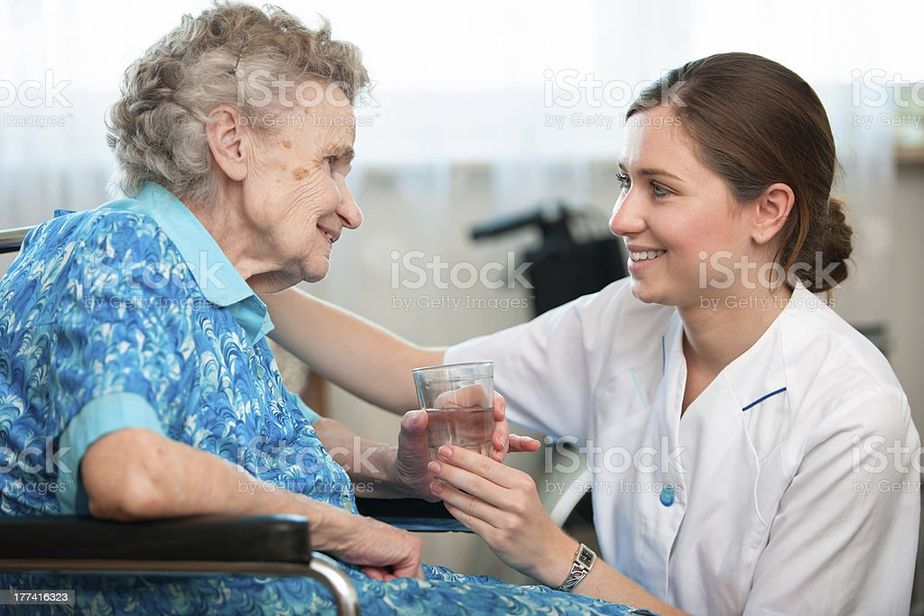 Woman taking care of elderly woman royalty-free stock photo