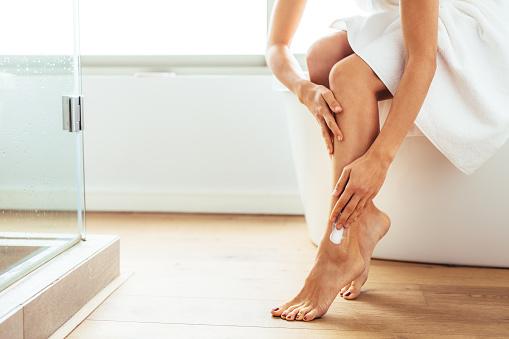Woman applying moisturizer to her legs after bath. Woman in bath towel sitting on bathtub in bathroom.