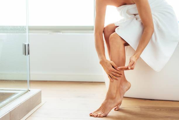 frau kümmert sich ihr körper nach bad - lotionen stock-fotos und bilder