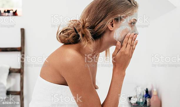 Side view shot of young woman applying facial cosmetic mask in bathroom.  Female taking care of her face skin.