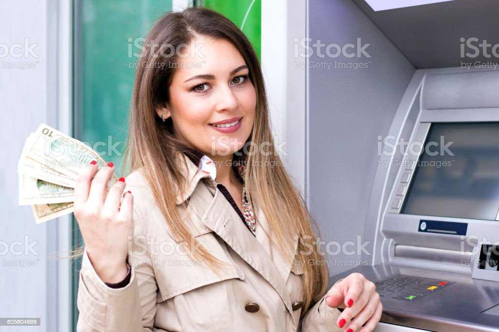 Woman taking cash from ATM stock photo