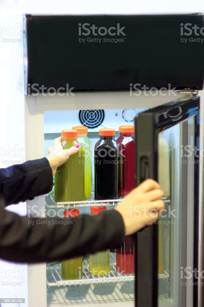 Woman taking cold juice from refrigerator stock photo