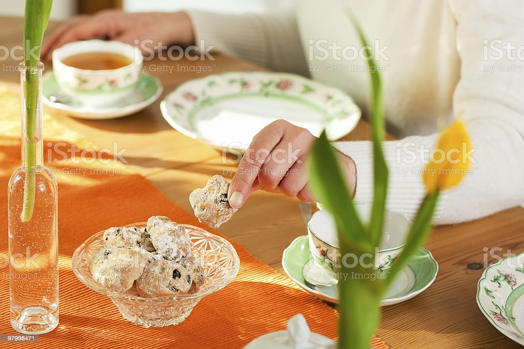 Woman taking cookies from coffee table royalty-free stock photo