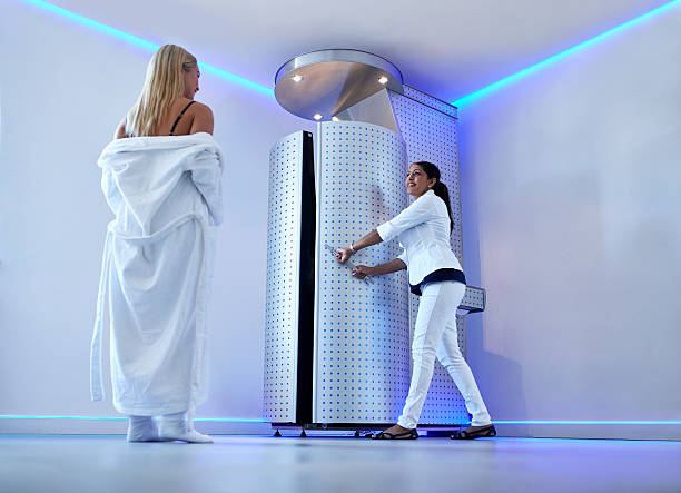 Woman taking cryosauna treatment at cosmetology clinic Full length portrait of woman in bathrobe at cosmetology clinic going for cryotherapy treatment in cryosauna. Nurse standing at the door of freezing capsule. cryotherapy stock pictures, royalty-free photos & images