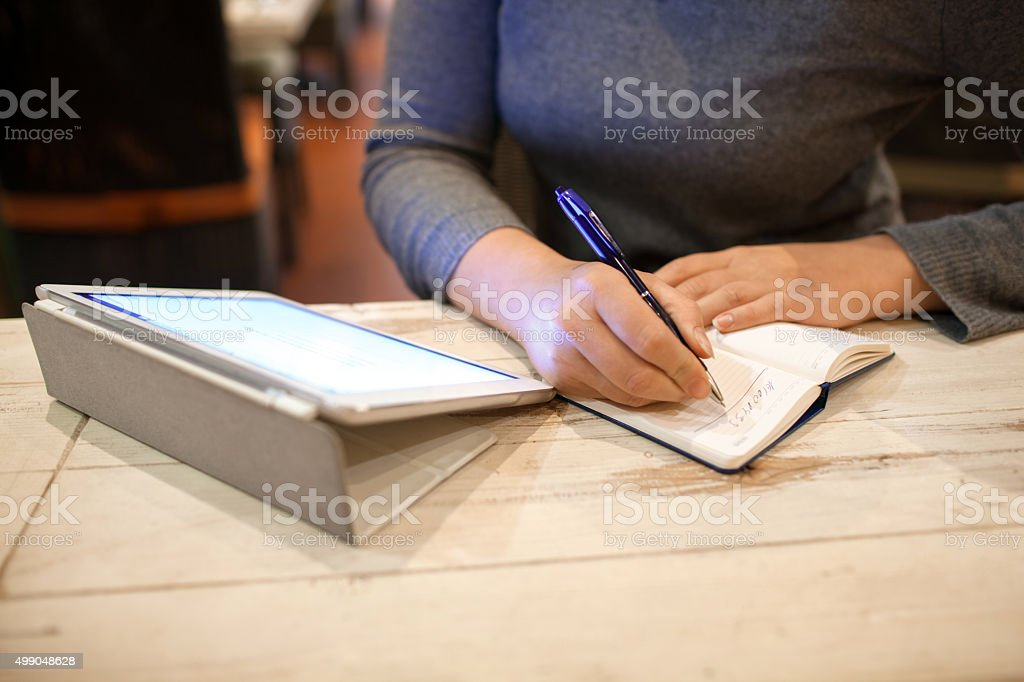 Woman taking down information in notebook stock photo