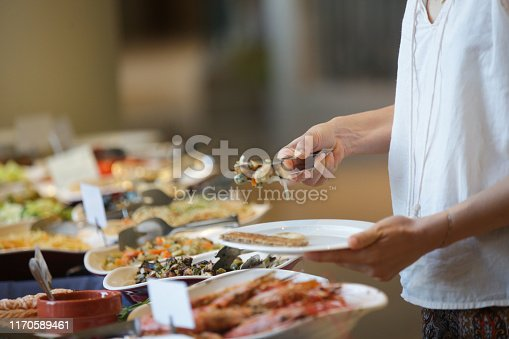 Woman taking food from a buffet line