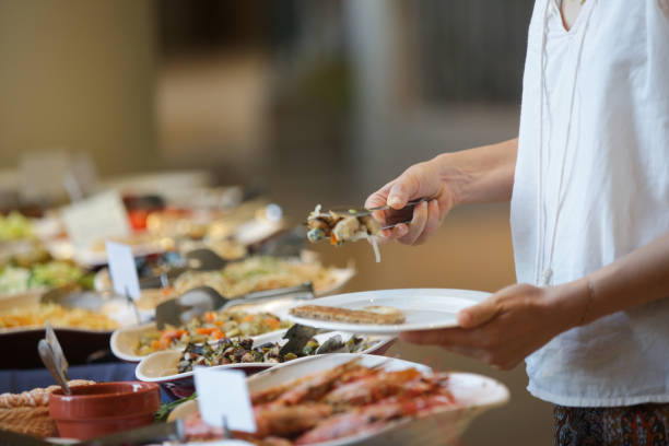 Woman taking food from a buffet line Woman taking food from a buffet line buffet stock pictures, royalty-free photos & images